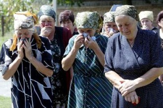 Relatives and neighbors grieve outside the house of an eight-year-old child hostage killed in the takeover of a school in Beslan, Russia.  Photo: Viktor Korotayev