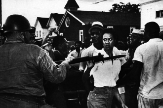 Gloria Richardson, local leader of the Cambridge movement, pushes away the bayonet of a National Guard officer