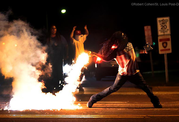 A protester in Ferguson throws back a tear gas canister towards the police.