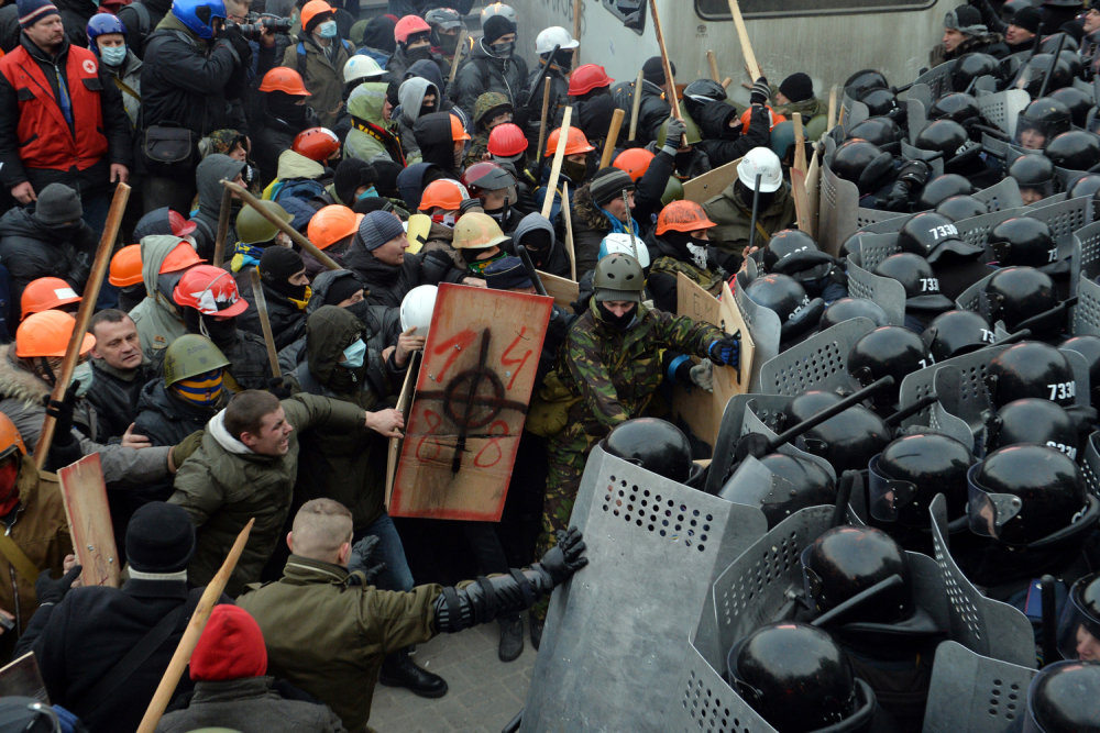 Rioters face off with Ukrainian riot police, a shield displaying white pride and Nazi logos. Photo: Sergei Supinsky / AFP / Getty Images