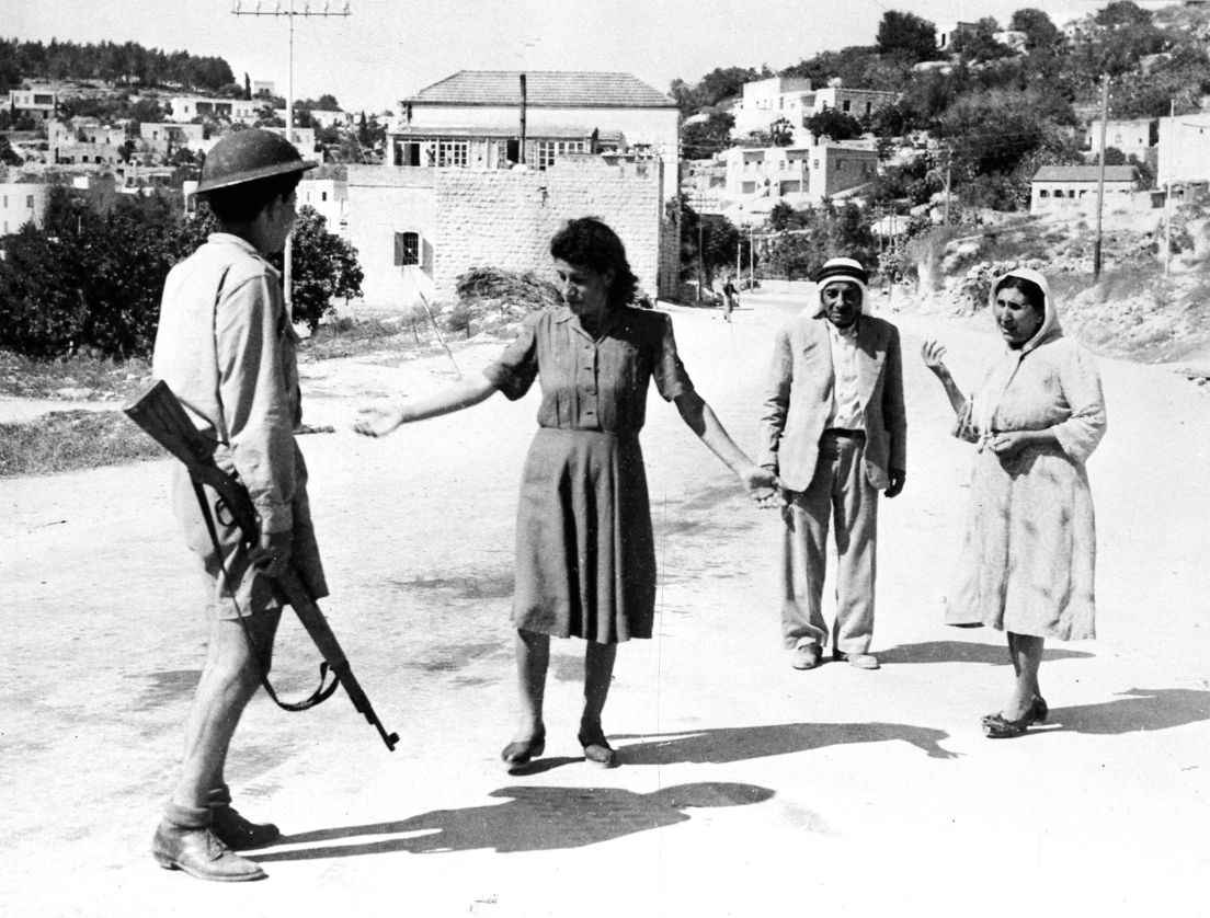 An Israeli soldier stops Palestinians in Nazareth, 1948, for traveling after the imposed curfew