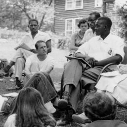 A study group at Highlander taking place outside. A Black man seated in a chair is speaking as a small multinational group listens, sitting in a circle.