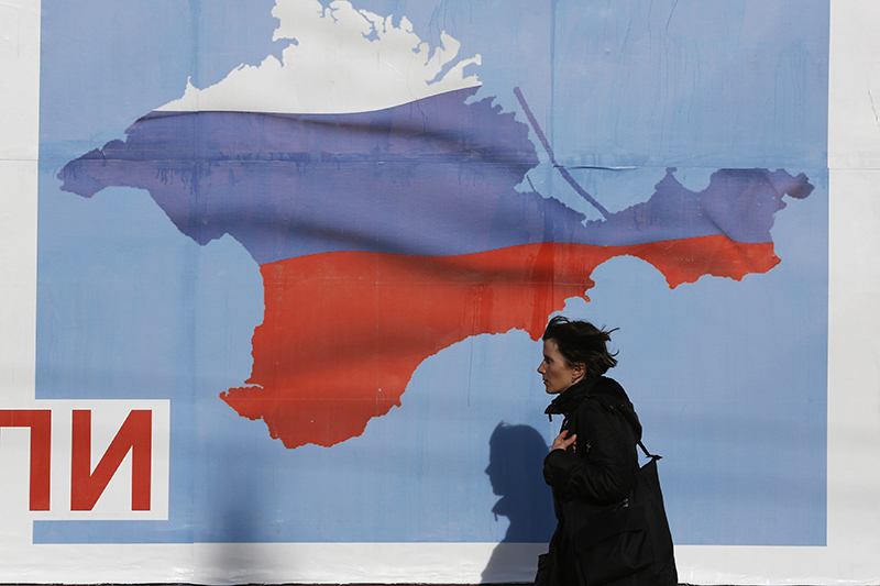 A woman walks by a poster in the Crimean port city of Sevastopol