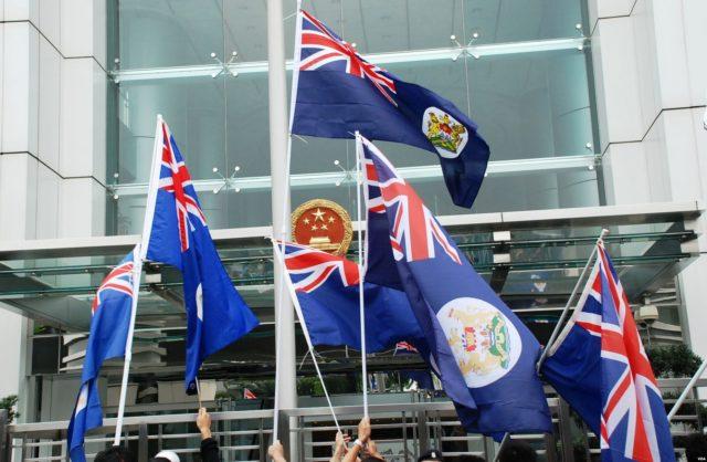 Hong Kong protesters wave the Hong Kong colonial flag